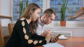 Os estudantes masculinos e fêmeas novos no telefone resolvem o problema no auditório da universidade Sentam-se com cadernos e video estoque