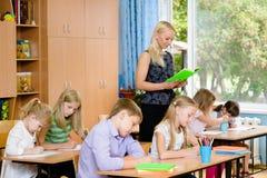 Os estudantes na classe escrevem atribuições que as lê um jovem Fotografia de Stock Royalty Free