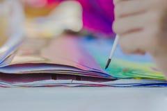 Os estudantes praticam pintar o cenário usando cores de cartaz Imagem de Stock