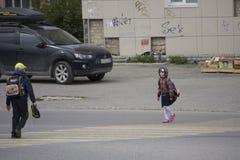 Os estudantes que cruzam a zebra na rua em Berezniki, Rússia, o 4 de setembro imagens de stock