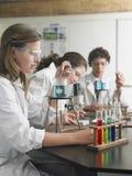 Os estudantes que importam-se para fora experimentam no laboratório Imagens de Stock Royalty Free