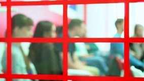 Os estudantes que sentam-se em sua mesa da escola e lesten o ticher A câmera remove através do vidro em portas da classe inglesa vídeos de arquivo