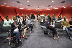 Os estudantes sentam-se enfrentando a câmera em uma sala de aula moderna da universidade Fotos de Stock