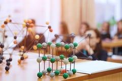 Os estudantes sentam-se na sala de aula e escutam-se uma leitura na ciência Modelo educacional molecular plástico Imagem de fundo imagens de stock royalty free