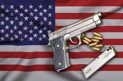 Os EUA atiram na bandeira das leis com arma e bala da pistola Fotos de Stock Royalty Free