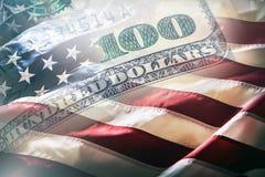 Os EUA embandeiram e dólares americanos Bandeira americana que funde no vento e em 100 dólares de cédulas no fundo Fotografia de Stock Royalty Free