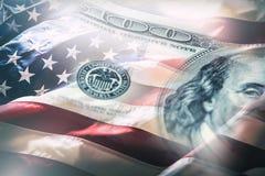Os EUA embandeiram e dólares americanos Bandeira americana que funde no vento e em 100 dólares de cédulas no fundo Imagem de Stock