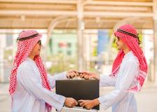 Os executivos árabes bem sucedidos que agitam as mãos trocam o saco sobre um negócio foto de stock royalty free
