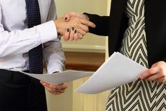 Os executivos agitam as mãos após ter assinado papéis do tratado imagem de stock