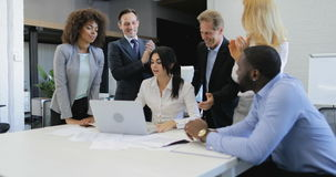 Os executivos agrupam a mulher de negócios de aplauso do congradulate das mãos que apresenta o projeto novo no laptop, equipe fel filme