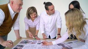 Os executivos agrupam na reunião e na apresentação no escritório moderno brilhante com o arquiteto do coordenador de construção e filme