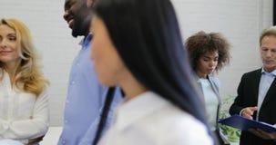 Os executivos agrupam o trabalho junto da equipe durante a reunião de sessão de reflexão no escritório moderno, mulher de negócio video estoque