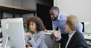 Os executivos agrupam o trabalho junto no computador que falam o escritório coworking moderno com discussão da equipe dos empresá filme
