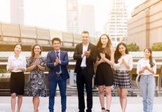 Os executivos aplaudem as mãos após ter terminado acima uma reunião exterior, grupo de executivos bem sucedido, achiev da diversi fotografia de stock