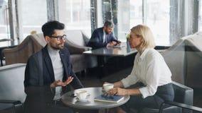 Os executivos bem sucedidos amadurecem o homem e a mulher que falam e que riem no café video estoque