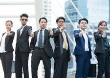 Os executivos bem sucedidos com polegares levantam e sorrir fotografia de stock