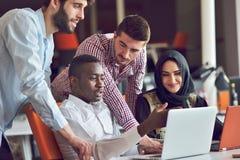 Os executivos contemporâneos multirraciais do trabalho conectaram com os dispositivos tecnologicos como a tabuleta e o portátil Imagem de Stock