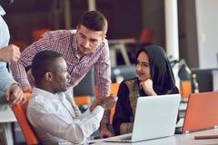 Os executivos contemporâneos multirraciais do trabalho conectaram com os dispositivos tecnologicos como a tabuleta e o portátil Imagens de Stock