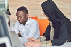 Os executivos contemporâneos multirraciais do trabalho conectaram com os dispositivos tecnologicos como a tabuleta e o portátil Fotografia de Stock Royalty Free