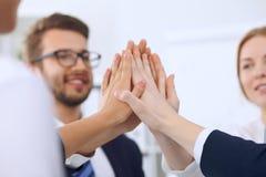 Os executivos de executivos do grupo agrupam trabalhos de equipa mostrando felizes e as mãos de junta ou a doação de cinco após a Imagem de Stock Royalty Free