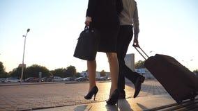 Os executivos deixam o aeroporto e o passeio com sua bagagem na rua da cidade Homem irreconhecível e mulher nos saltos vídeos de arquivo