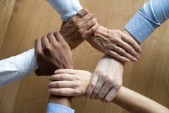 Os executivos diversos da equipe que agarra as mãos, fecham-se acima da vista superior fotografia de stock royalty free