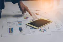 Os executivos entregam o trabalho com uma tabuleta no backg branco da tabela Fotos de Stock Royalty Free