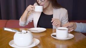 Os executivos falam e bebem o café ao sentar-se no restaurante filme