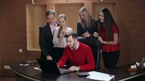 Os executivos felizes comemoram o sucesso que olha a tela do portátil no escritório
