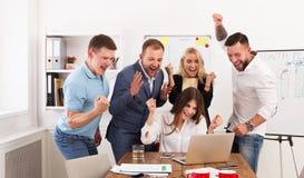 Os executivos felizes da equipe comemoram o sucesso no escritório Imagem de Stock