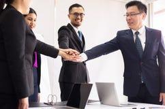 Os executivos juntam-se ao sucesso das mãos para negociar no escritório, trabalho da equipe para conseguir objetivos, entregam a  foto de stock royalty free