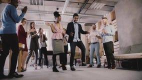 Os executivos multi-étnicos comemoram a realização do negócio no dance party ocasional do escritório no movimento lento coworking filme