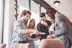 Os executivos novos bem sucedidos são de fala e de sorriso durante a ruptura de café no escritório imagens de stock