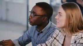 Os executivos positivos novos da raça misturada, homem e mulher, cooperam discutindo o projeto atrás da tabela no escritório m video estoque