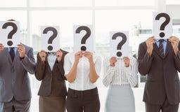 Os executivos que guardam o ponto de interrogação assinam dentro o escritório foto de stock