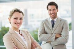 Os executivos que levantam com braços cruzaram o sorriso na câmera Fotografia de Stock Royalty Free