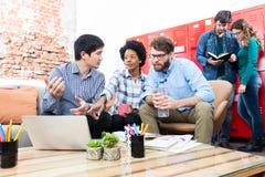 Os executivos que sentam a mistura diversa do escritório criativo do sofá competem imagem de stock royalty free