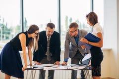 Os executivos recolheram junto em uma tabela que discutem uma ideia foto de stock