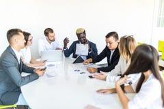 Os executivos team em documentos de trabalho da reunião junto no escritório Reunião final do projeto imagem de stock