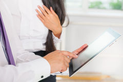 Os executivos vestiram-se no PC de utilização branco da tabuleta no escritório Imagens de Stock Royalty Free