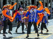 Os executores coloridamente vestidos dançam abaixo de uma rua de Cusco durante a parada do primeiro de maio no Peru Foto de Stock
