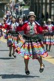 Os executores coloridamente vestidos dançam abaixo de uma rua de Cusco durante a parada do primeiro de maio no Peru Imagens de Stock Royalty Free