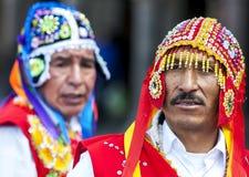 Os executores coloridamente vestidos dançam abaixo de uma rua de Cusco durante a parada do primeiro de maio no Peru Fotografia de Stock