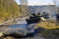 Os exercícios militares, exército do russo, os tanques blindados t-90 quebraram através da lama com o botânico foto de stock