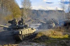 Os exercícios militares, exército do russo, os tanques blindados t-90 quebraram através da lama com o botânico fotografia de stock royalty free