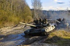 Os exercícios militares, exército do russo, os tanques blindados t-90 quebraram através da lama com o botânico fotografia de stock