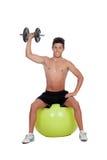Os exercícios praticando de homem forte com pesos sentam-se em uma bola Imagem de Stock Royalty Free