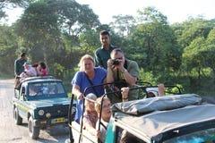 Os exploradores do safari do jipe no parque nacional de Jaldapara na Índia imagens de stock