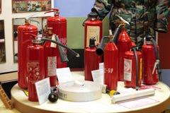 Os extintores de modelos diferentes estão na tabela Imagens de Stock Royalty Free
