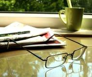 Os eyeglasses, o jornal na tabela e Fotos de Stock Royalty Free